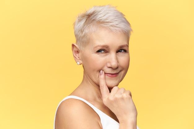Hmm, laat me even nadenken. geïsoleerd beeld van aantrekkelijke gepensioneerde vrouw met kort kapsel die de vinger op haar lippen houdt, iets probeert te raden, met een doordachte verdachte gezichtsuitdrukking