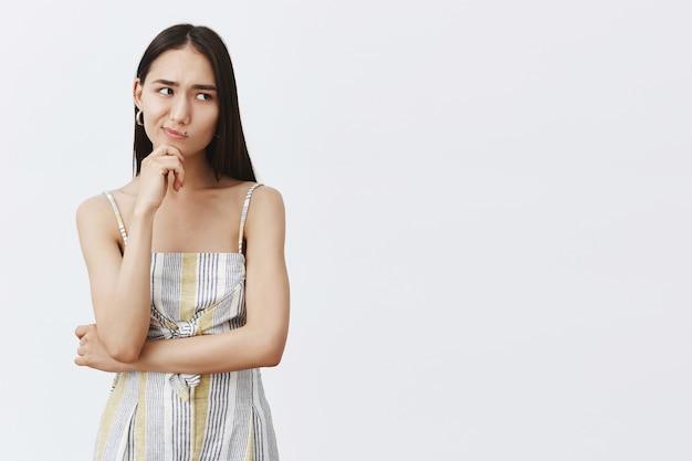 Hmm, laat me even nadenken. portret van twijfelachtig goed uitziende aziatische vrouw in bijpassende trendy outfit, grijnzend en naar rechts staren terwijl hand op kin, denken, aarzelend over grijze muur