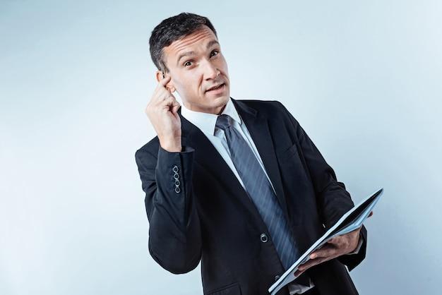 Hmm. nadenkende mannelijke ondernemer die zijn tempel aanraakt met een pen terwijl hij over een aantal bedrijfsstrategieën nadenkt en ze opschrijft in een notitieboekje.