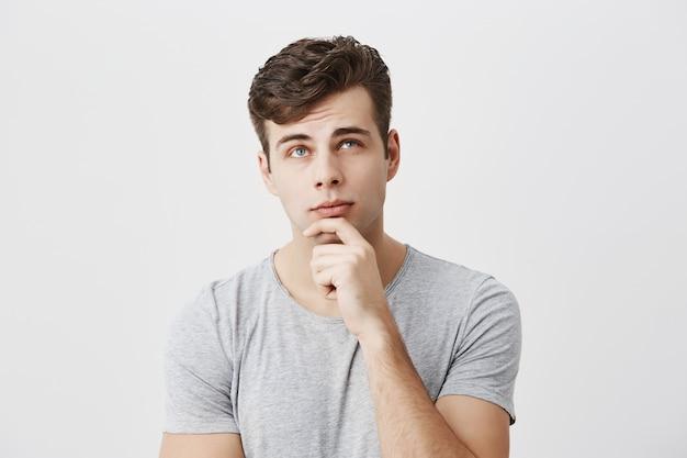 Hmm niet slecht. geconcentreerde, doordachte mannelijke student die zijn kansen om te slagen voor het examen evalueert, de kin op de hand houdt, probeert te beslissen wat hij verdient. mensen, levensstijl, gezichtsuitdrukkingen.