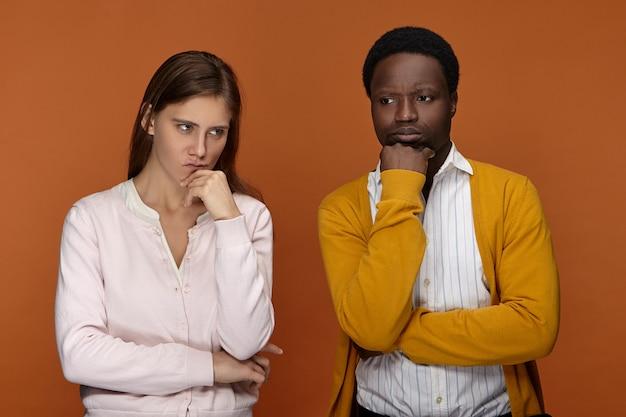 Hmm. portret van doordachte jonge blanke vrouw met lang haar en haar peinzende donkere mannelijke collega ontwikkelt creatieve ideeën voor startprojecten, diep in gedachten uitdrukkingen