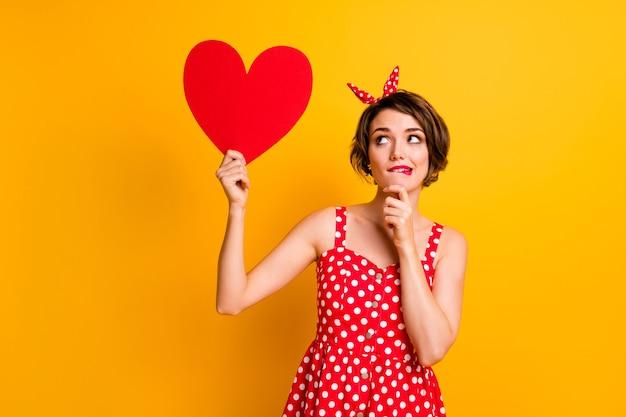 Hmm vriendje houdt van mij? peinzend meisje vasthouden rood groot papercard hart krijgen 14 februari 8 maart denken aanraken handen kin proberen beslissen dilemma dragen retro stijl kleding geïsoleerd gele kleur muur