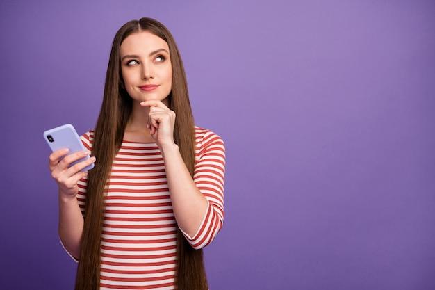Hmm welk bericht op sociaal netwerk ... portret van een minded geïnteresseerd meisje kijk copyspace aanraking hand kin denk gedachten verwondering overwegen dragen trui geïsoleerd over violette kleur muur