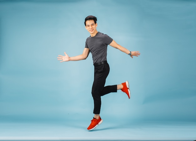 Hnadsome aziatische man springen geïsoleerd over blauwe muur.
