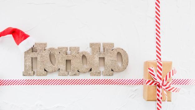 Ho ho ho-inscriptie in de buurt van kerstmuts en geschenkdoos
