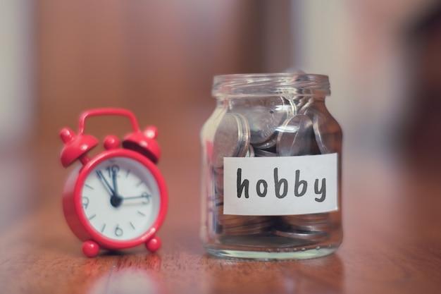 Hobby besparingen concept - glazen pot met munten en inscriptie.