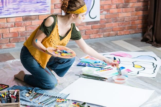 Hobby en recreatie. zijaanzicht van linkshandige kunstenaar die abstracte kunstwerken schildert
