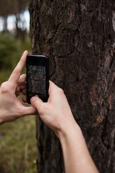 Hobby natuurfotografie. man die mobiele foto's maakt in het bos