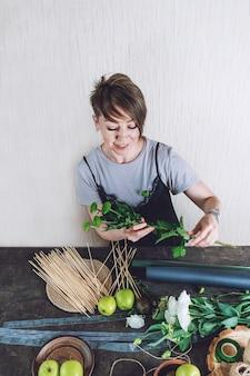 Hobby's en activiteiten, kunsten en ambachten tijdens het coronavirus. bloemist vrouw maakt fruit eetbaar boeket. natuurlijkheid, bloemschikken, bloemistentrucs, tips, trends.