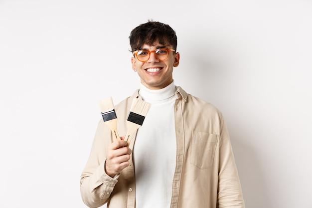 Hobby's en vrijetijdsconcept. stijlvolle jonge man in glazen schilderij penselen tonen en glimlachen, uitnodigend om iets te schilderen, staande op een witte muur.