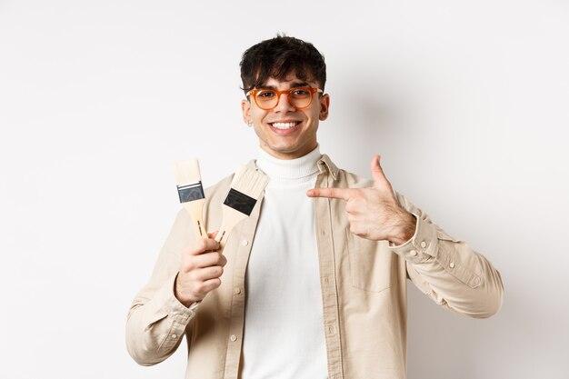 Hobby's en vrijetijdsconcept. vrolijke jonge man in glazen wijzend op schilderij penselen, appartement renoveren, staande op een witte muur.
