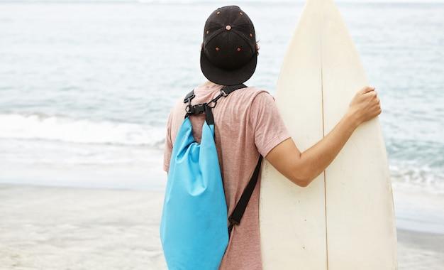 Hobby-, vrijetijds- en zomervakanties. terug geschoten van stijlvolle jonge surfer die snapback en rugzak dragen die golven gaan berijden terwijl het hebben van vakantie in tropisch land