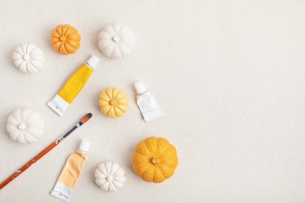 Hobbyachtergrond met handgemaakte gipspompoenen, penselen en kunstaccessoires