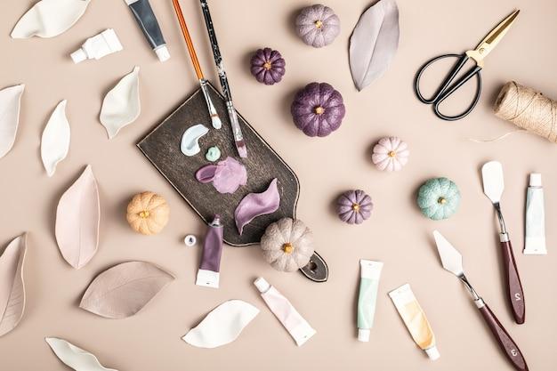 Hobbyachtergrond met handgemaakte kleibladeren en pompoenen, penselen en kunstaccessoires diy, ambachtelijke decoratie voor herfstvakanties plat lag, bovenaanzicht