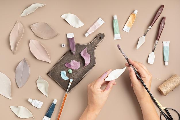 Hobbyachtergrond met handgemaakte kleibladeren, penselen en kunstaccessoires diy, ambachtelijke decoratie voor herfstvakanties plat lag, bovenaanzicht