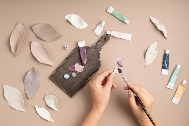 Hobbyachtergrond met handgemaakte kleibladeren, penselen en kunstaccessoires