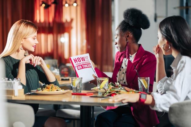 Hoe drie alleenstaande modieuze zakenvrouwen te vinden die een boek lezen over het vinden van een echtgenoot