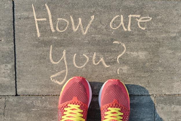 Hoe gaat het, geschreven op grijze stoep met vrouwenbenen in sneakers