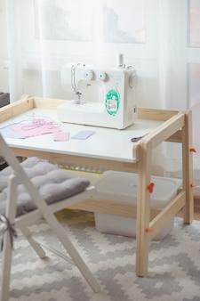 Hoe gezichtsmasker te naaien, beschermend masker naaiproces, stukjes gestippelde doek, draden en naaimachine op witte tafel met witte stoel.