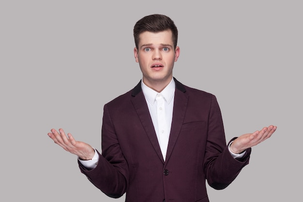 Hoe heb je dit gedaan? portret van een verwarde knappe jongeman in violet pak en wit overhemd, staand, camera kijkend met opgeheven armen en vragend. indoor studio opname, geïsoleerd op een grijze achtergrond.