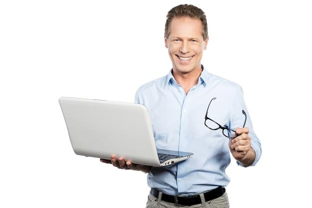Hoe kan ik u helpen? gelukkig volwassen man in shirt met laptop en glimlachend terwijl hij tegen een witte achtergrond staat