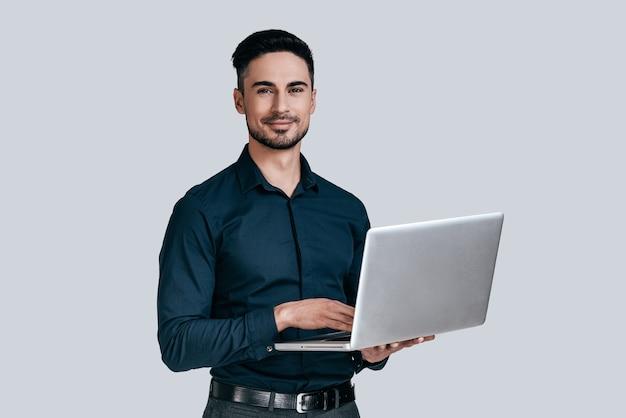 Hoe kan ik u helpen? knappe jonge man in shirt die op laptop werkt