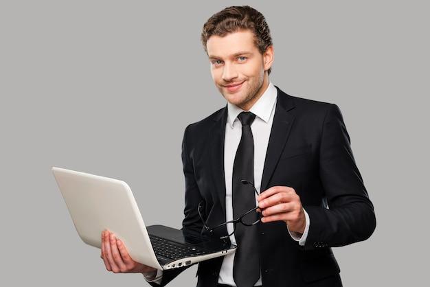 Hoe kan ik u helpen? zelfverzekerde jonge man in formalwear die op laptop werkt terwijl hij tegen een grijze achtergrond staat