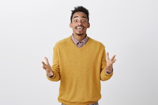 Hoe kon je dit geweldige feest missen? portret van overweldigde aantrekkelijke afrikaanse man met afro kapsel in gele trui gebaren met gespreide handpalmen, pratend met opwinding over favoriete zanger