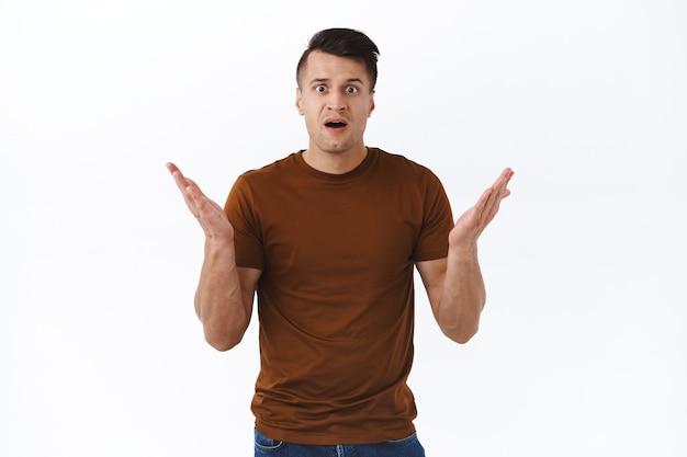 Hoe kon je. portret van een geschokte en gefrustreerde knappe man die ontzet de hand schudt