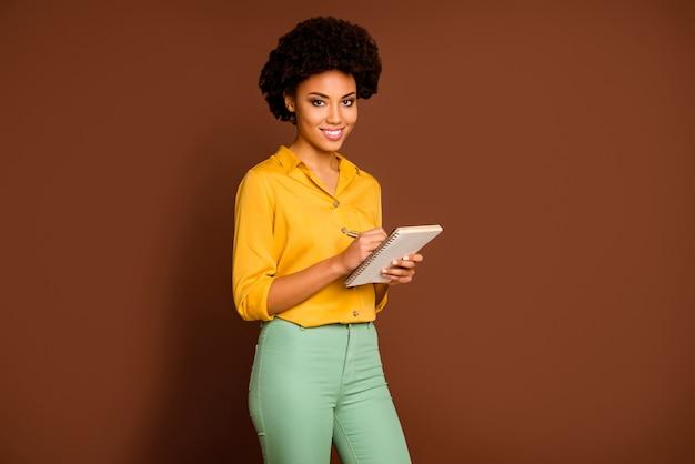 Hoe kun je inspiratie opdoen? foto van mooie donkere huid krullende dame auteur houden dagboek opmerkingen schrijvers opleiding dragen geel shirt groene broek geïsoleerde bruine kleur
