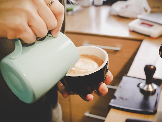 Hoe latte kunst te maken door barista focus in melk en koffie