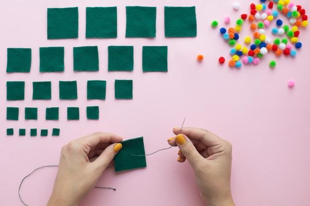 Hoe maak je thuis een kleine vilten kerstboom. stap voor stap instructies. handen maken gemakkelijk te volgen doe-het-zelf-project.
