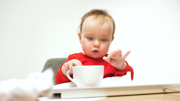 Hoe moe ik ben. kind babymeisje zit met toetsenbord van moderne computer of laptop in het wit