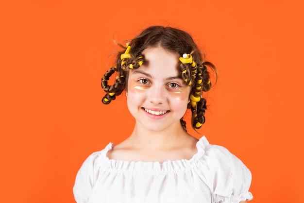 Hoe papillote te kiezen. oogtherapie patch. schoonheid en mode. klein meisje heeft haarkrulspelden papillotes. kapsalon voor kinderen. gezond lang kapsel. haarverzorging voor kinderen. klein kind met haarroller.