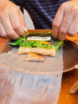 Hoe te eten, met de hand verpakt vietnamees gegrild vlees of gehaktballen wrap set met groenten en zoete saus (nham neung)