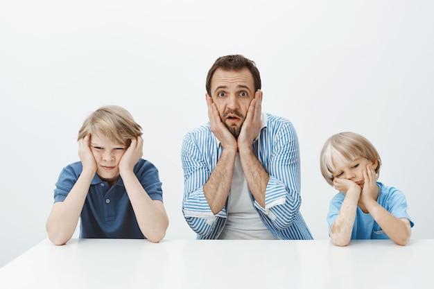Hoe ze snel opgroeiden. portret van geschokt angstige europese vader zitten met zonen, hand in hand op gezicht en kaak laten vallen