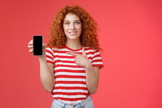 Hoe zit het met deze app. roodharige krullend vriendelijk schattig meisje help vriend om oufit online winkel te vinden, houd smartphone aanwijzend telefoonscherm glimlachend in grote lijnen aanbevelen sociale media fotofilter, rode achtergrond.
