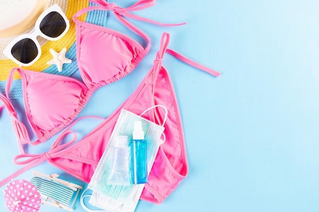 Hoed, bikini, zonnebril, medisch masker en handdesinfecterend middel. zomer, vakantie
