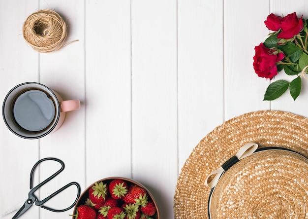 Hoed bloemen koffie en rozen op witte houten achtergrond bovenaanzicht