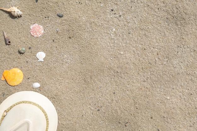 Hoed en schelpen op een zand. bovenaanzicht, kopieer ruimte