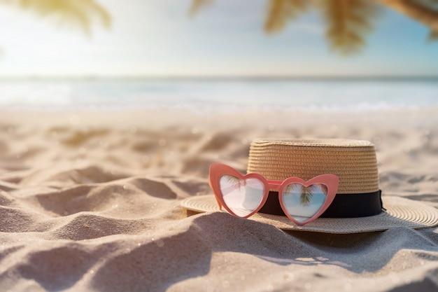 Hoed en zonnebril op het tropische zandstrand met exemplaarruimte, het concept van de de zomervakantie