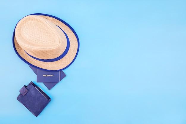 Hoed, paspoorten en portemonnee op blauw met kopie ruimte