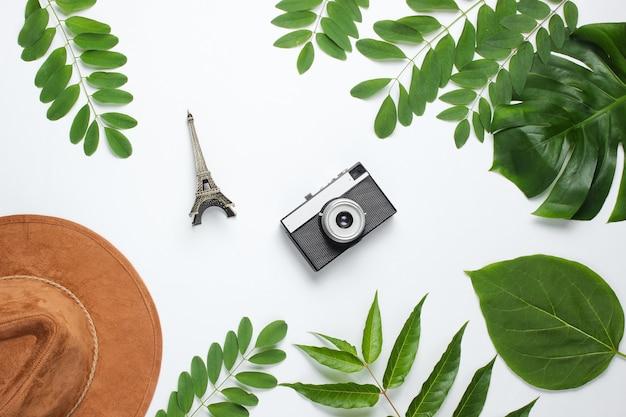 Hoed, retro camera, beeldje van de eiffeltoren op witte achtergrond met groene bladeren.