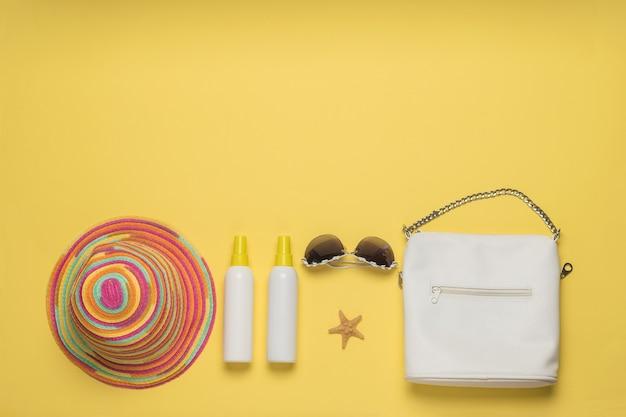 Hoed, tas, bril en zonnebrandcrème op een gele achtergrond. vakantieconcept. plat leggen. plaats voor tekst.