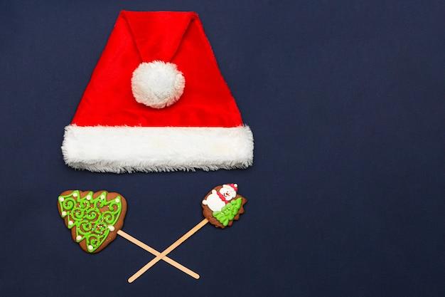 Hoed van de kerstman en peperkoek kerstkoekjes op f donkerblauwe achtergrond
