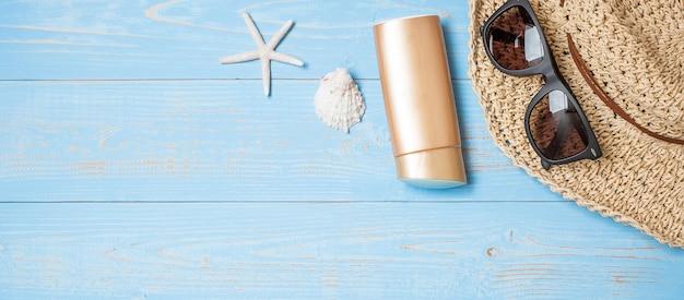 Hoed, zonnebrandcrème, zonnebril en schelp op blauw