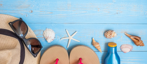 Hoed, zonnebrandcrème, zonnebril, slippers en schelp op blauw