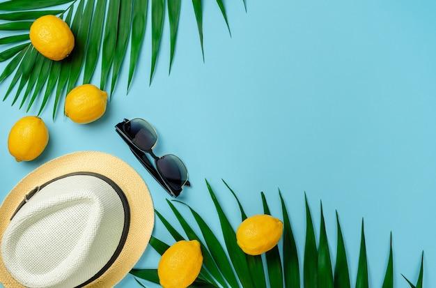 Hoed, zonnebril en citroenen met palmbladeren. zomer achtergrond, plat lag, bovenaanzicht.