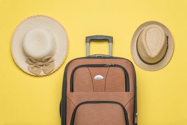Hoeden voor heren en dames en een reiskoffer op een gele achtergrond. plat leggen.
