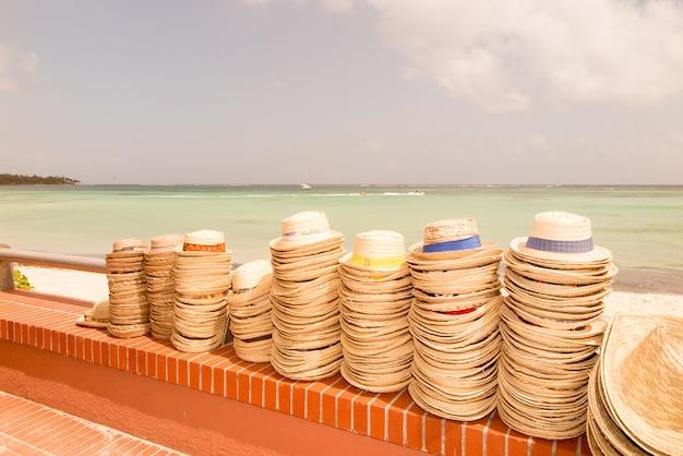 Hoedenverkoper staat op het tropische strand van de caraïben